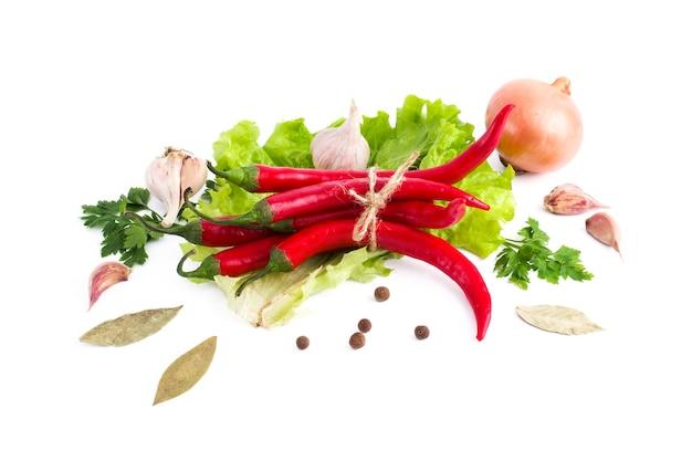 Verse groenten op een witte achtergrond bittere rode paprika en uien met greens op een witte achtergrond.