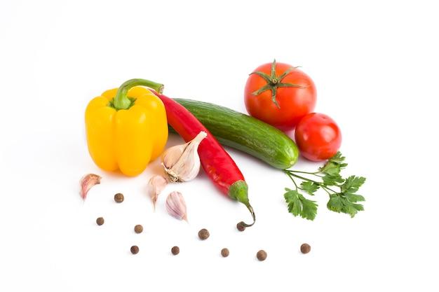 Verse groenten op een witte achtergrond.gele peper, groene komkommer, rode tomaat en bittere peper op een witte achtergrond.