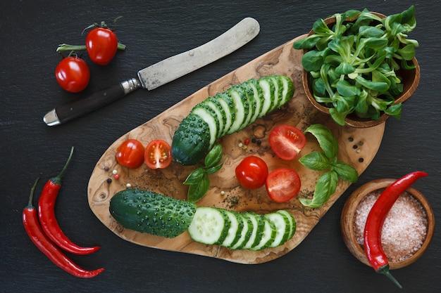 Verse groenten op houten snijplank met mes op zwart betonnen achtergrond