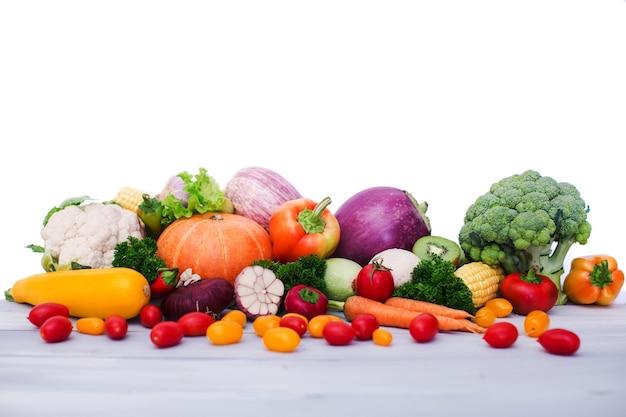 Verse groenten op houten tafel. geïsoleerd op witte achtergrond.
