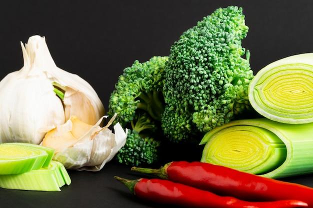 Verse groenten op zwarte achtergrond: broccoli, prei, chili peper en knoflook. gezond eten.