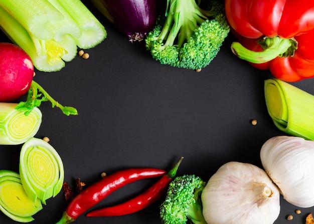 Verse groenten op zwarte achtergrond met exemplaarruimte. gezond eten.