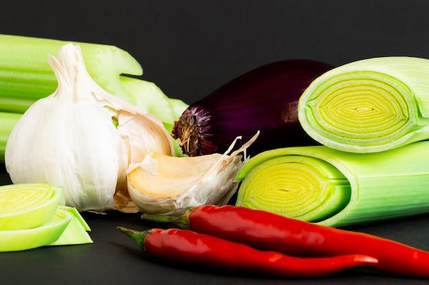 Verse groenten op zwarte achtergrond: selderij, prei, rode ui, chili peper en knoflook.