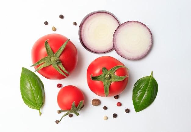 Verse groenten, tomaten, basilicum, uien en zwarte peper op een witte achtergrond. het concept van heerlijk en gezond eten, ingrediënten om te koken
