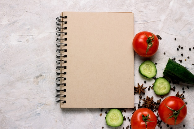 Verse groenten, tomaten, komkommers, kruiden, kladblok voor voedselrecepten op de lichte achtergrond.