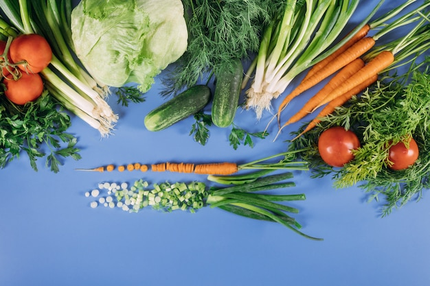 Verse groenten voor salade op een blauwe achtergrond.