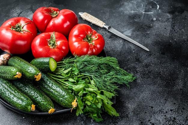Verse groenten voor zomer groene salade, rode tomaten, komkommers, peterselie, kruiden. zwarte achtergrond. bovenaanzicht. ruimte kopiëren.