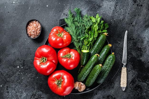 Verse groenten voor zomer groene salade, rode tomaten, komkommers, peterselie, kruiden. zwarte achtergrond. bovenaanzicht.