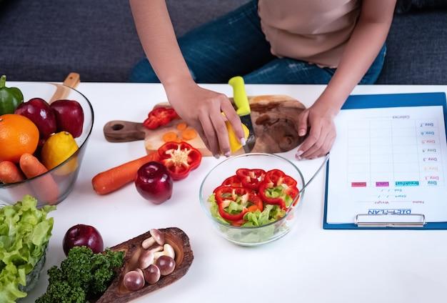 Verse groentes bereidde zich voor op salade maaltijd door vrouw, gezond voedsel, goed voor het leven, slakom zet naast vaag dieetplan schema