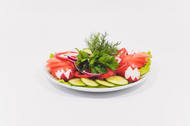 Verse groentesalade die op witte achtergrond wordt geïsoleerd.