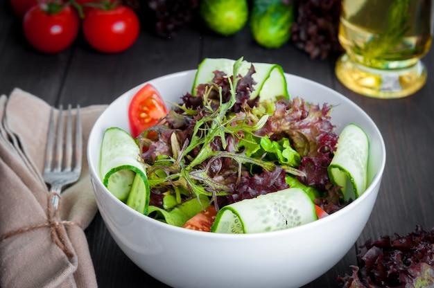 Verse groentesalade, gezonde voeding, biologische komkommers, tomaten en slablaadjes