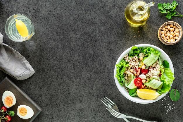 Verse groentesalade in een plaat op zwarte oppervlakte