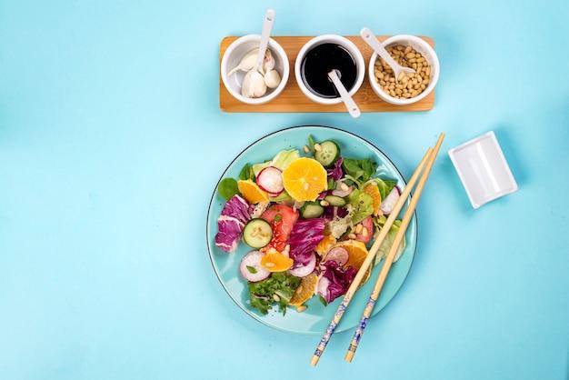 Verse groentesalade met diverse vulling op blauwe achtergrond, hoogste mening, grens.