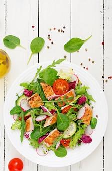 Verse groentesalade met gegrilde kipfilet - tomaten, komkommers, radijs en meng slablaadjes. kip salade. gezond eten. bovenaanzicht