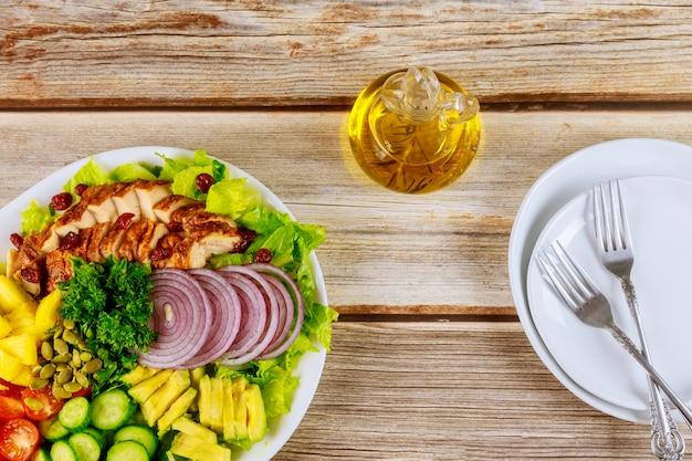 Verse groentesalade met geroosterde kippenborst, tomaten, komkommers en olijfolie in fles