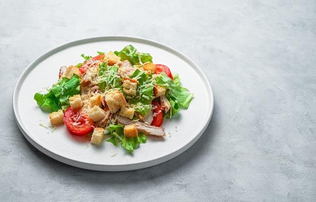 Verse groentesalade met kipfilet op een grijs bureau met ruimte om te kopiëren
