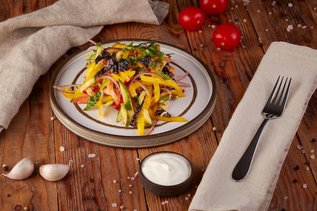Verse groentesalade met olie, houten achtergrond