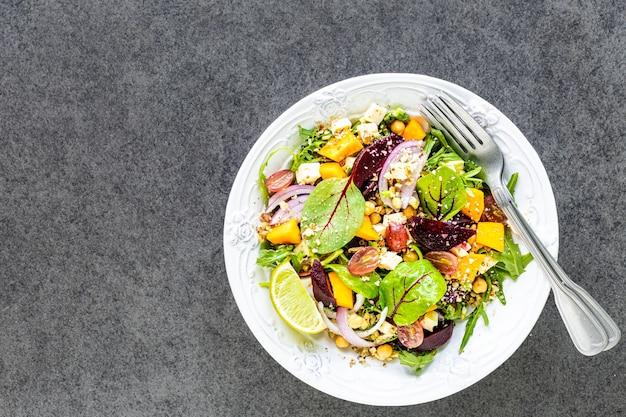Verse groentesalade met rode biet, rucola, rode ui, zuring, kikkererwten, pompoen en druiven in een witte plaat op zwart. bovenaanzicht