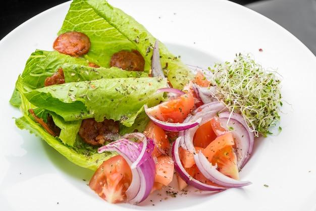 Verse groentesalade met tomaat, andijvie en ui.