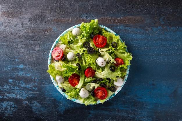 Verse groentesalade met tomaten, kaas en olijven. bovenaanzicht