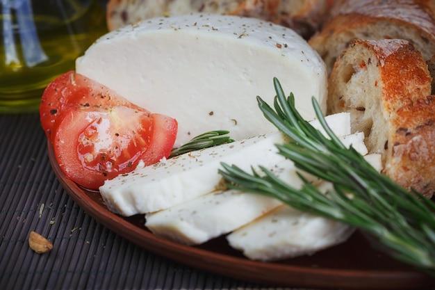 Verse groentesalade met tomaten, komkommers en uien. geserveerd met kaas, groenten, olijfolie en brood