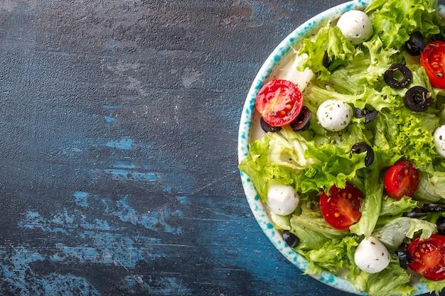 Verse groentesalade met tomaten, mozzarella en zwarte olijven. bovenaanzicht, tekstruimte