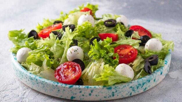 Verse groentesalade met tomaten, mozzarellakaas en olijven.
