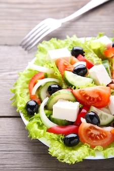 Verse groentesalade met vork op grijze achtergrond