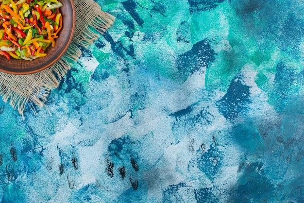 Verse groentesalade op een plaat op de jute, op de blauwe achtergrond.