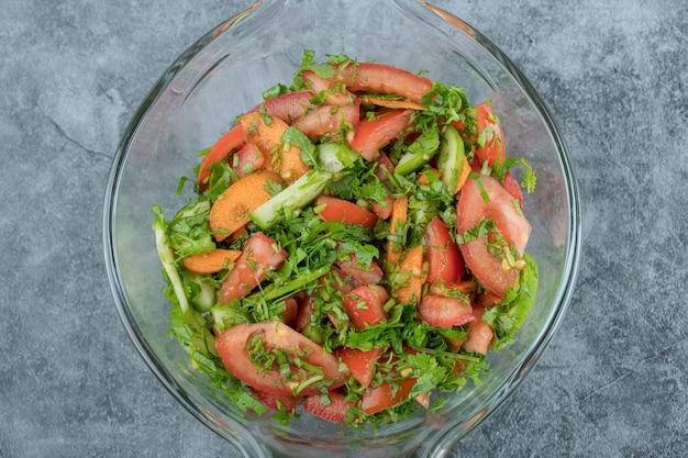 Verse groentesalade op in glazen kom.