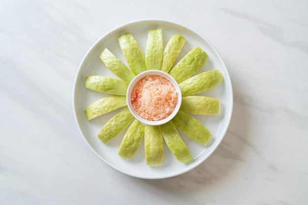 Verse guave gesneden met chili en zout dompelen