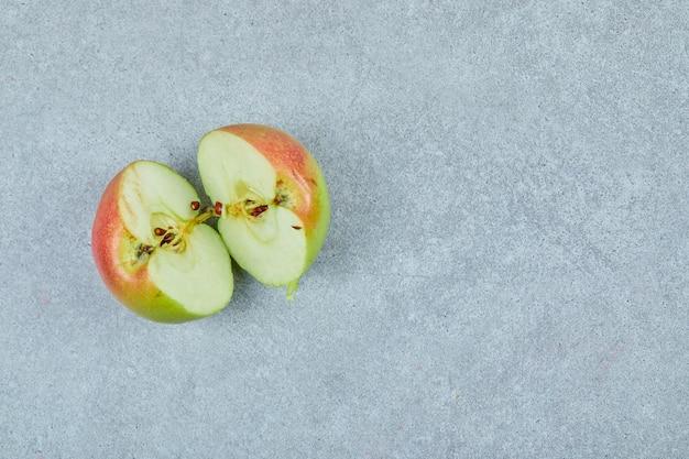 Verse half gesneden appel op grijs.