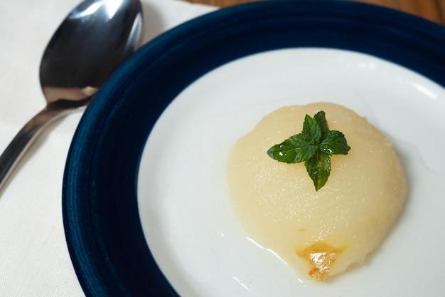 Verse halve peren geserveerd met zoete siroop en muntblaadjes.