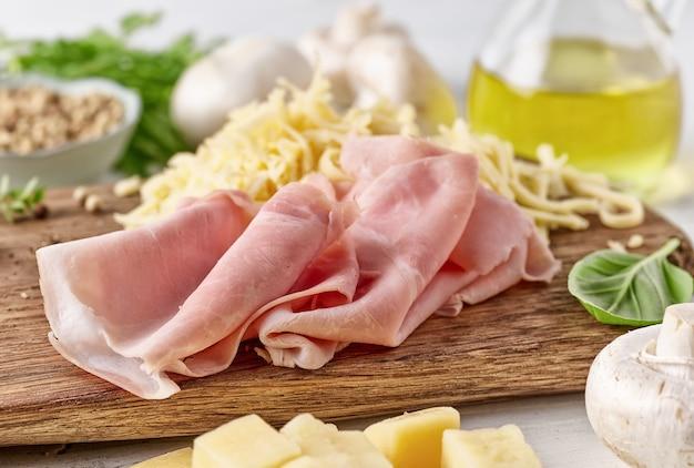 Verse ham en geraspte kaas voor het maken van pizza op houten snijplank