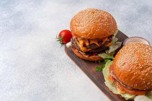 Verse hamburger geserveerd op een houten bord op een grijze ondergrond