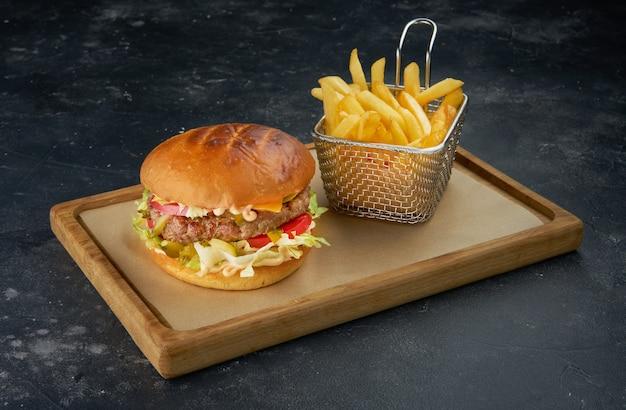 Verse hamburger met mandje met frietjes op donkere tafel met kom tomatensaus