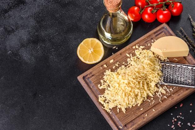 Verse harde kaas geraspt op een grote rasp op een houten snijplank op een donkere betonnen achtergrond
