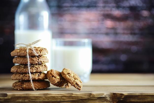 Verse havermoutkoekjes met melk op een textuur houten achtergrond. kerst peperkoekkoekje en een glas melk.
