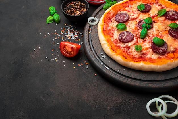Verse, heerlijke pizza en ingrediënten op een bruine achtergrond. bovenaanzicht met kopie ruimte. het concept van culinaire achtergronden.