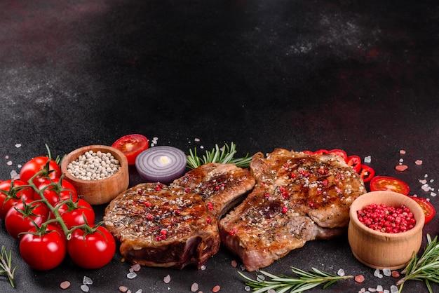 Verse heerlijke sappige biefstuk op de botten met groenten en kruiden. grill van het varkensvlees de sappige lapje vlees op donkere lijst