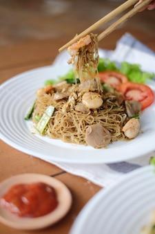 Verse heerlijke vietnamese noedels vermicelli met stukjes gehaktballetjes en tomaat op de witte plaat