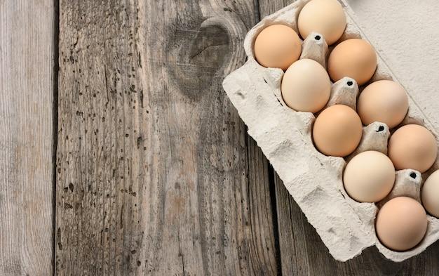 Verse hele bruine eieren in papieren verpakkingen op een grijze houten tafel, bovenaanzicht, kopie ruimte