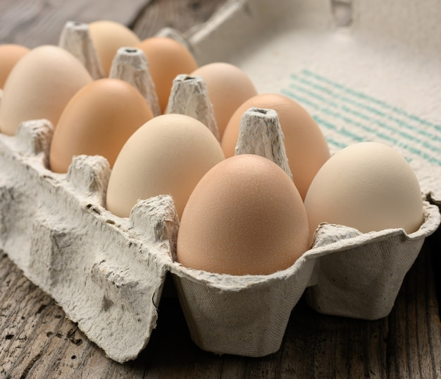 Verse hele bruine eieren in papieren verpakkingen op een grijze houten tafel, close-up