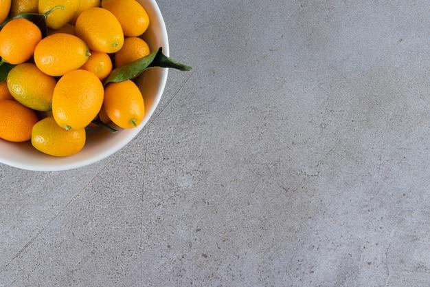 Verse hele citrusvruchten cumquatvruchten met bladeren die in kom worden geplaatst