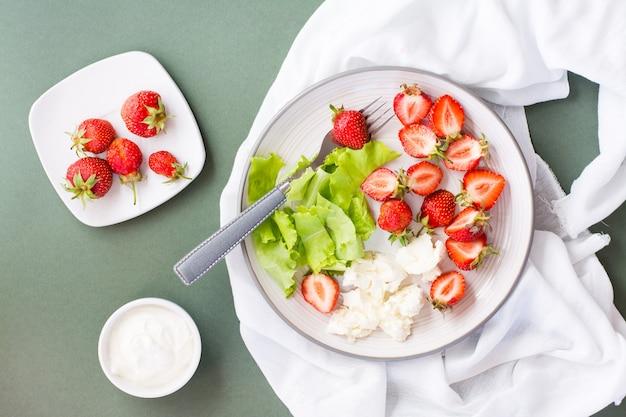 Verse hele en gesneden aardbeien, kwark en sla op een bord en zure room in een kom op een groene tafel.