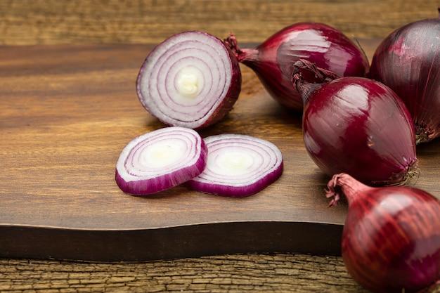 Verse hele rode uien zijn als in plakjes gesneden op een houten snijplank op een houten tafel.
