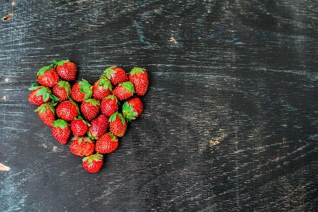 Verse het hartvorm van de aardbeienserie op oude houten achtergrond