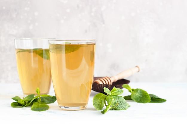 Verse hete pepermunt kruidenthee in glazen met verse muntblaadjes en honing