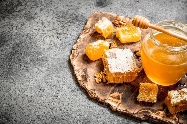Verse honing in een pot en honingraat met noten op rustieke tafel.