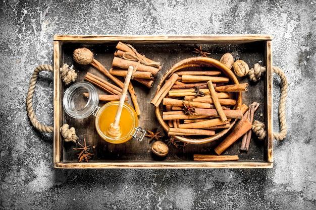 Verse honing met de kaneelstokjes in een kom. op rustieke achtergrond.